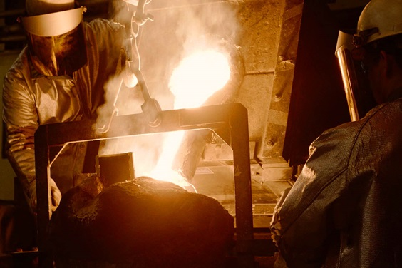 Two Sulzer employees in the foundry pouring metal in a mold