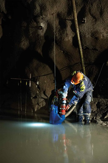 Man is using dewatering pump in cave