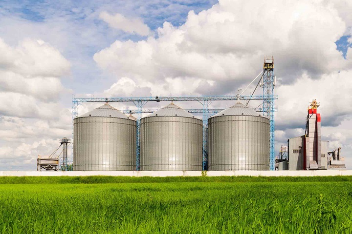 Agricultural silo with green meadow