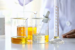 Person in laboratory with oleochemicals