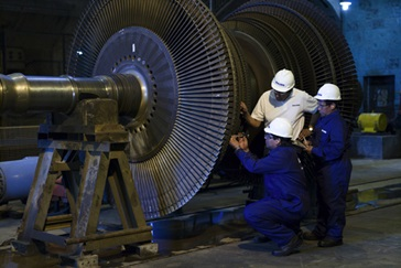 Field service experts at a customer site inspecting a steam turbine rotor