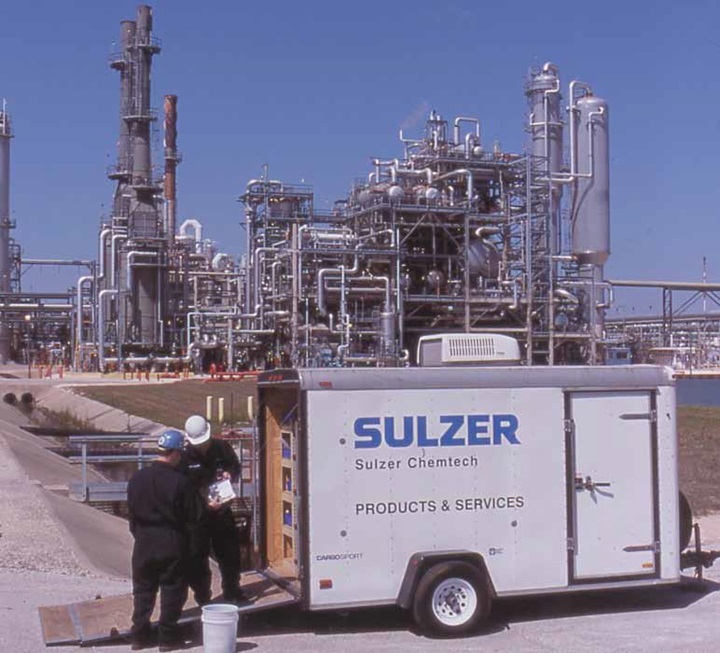 Two Sulzer Chemtech employees with a trailer in front of a customer mill