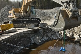 Excavator holding drainage pump in pit at site for dewatering in construction