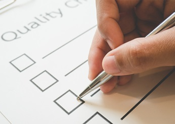Pen ticking a box on a quality checklist