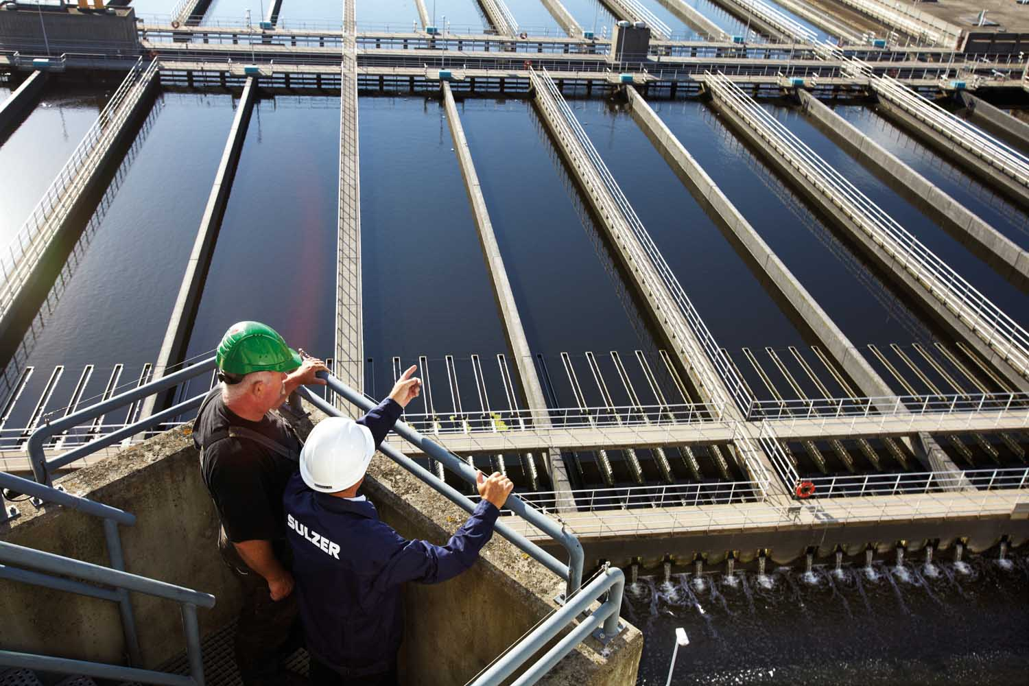 Sulzer employee and customer look out over wastewater treatment plant in Denmark